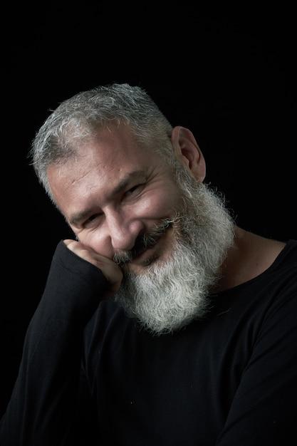 Ritratto di un uomo dai capelli grigi brutale sorridente con una barba lussureggiante dai capelli grigi su sfondo nero, messa a fuoco selettiva Foto Premium