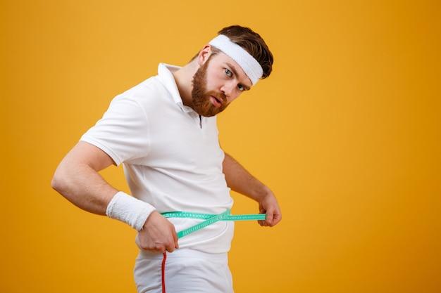 Ritratto di un uomo di sport che misura la sua vita con nastro adesivo Foto Gratuite