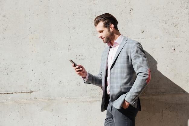 Ritratto di un uomo felice in giacca tenendo il telefono cellulare Foto Gratuite