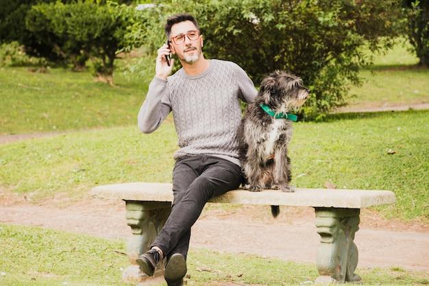 Ritratto di un uomo moderno seduto nel parco con il suo cane parlando sul telefono cellulare Foto Gratuite