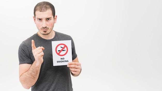 Ritratto di un uomo serio che tiene segno non fumatori che punta il dito verso la telecamera Foto Gratuite
