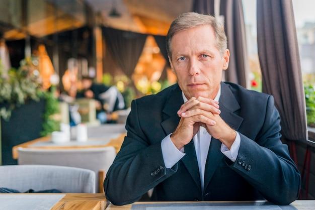 Ritratto di un uomo serio seduto nel ristorante Foto Gratuite