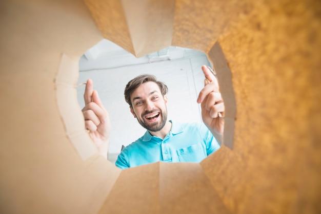 Ritratto di un uomo sorridente che guarda all'interno del sacchetto di carta Foto Gratuite