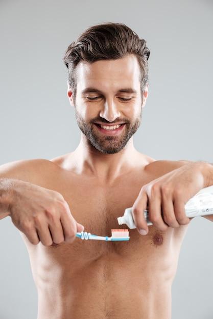 Ritratto di un uomo sorridente che mette dentifricio in pasta su uno spazzolino da denti Foto Gratuite