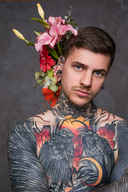 Ritratto di un uomo tatuato con piercing nelle orecchie e naso in piedi su sfondo grigio Foto Gratuite