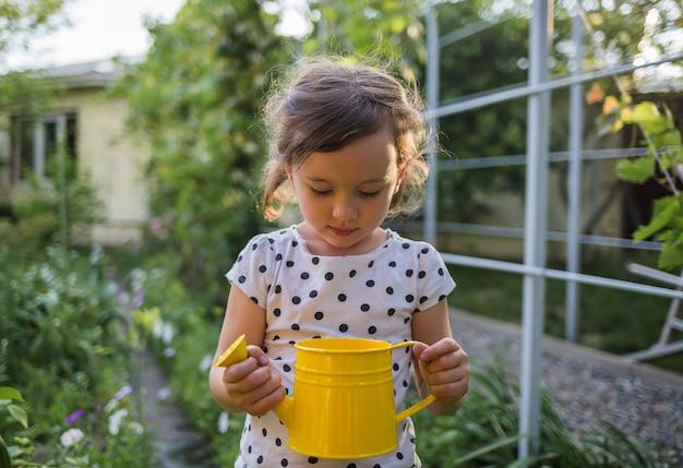 Ritratto di una bambina al tramonto che sta nel giardino in un annaffiatoio giallo Foto Premium