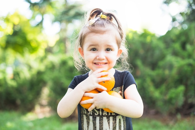 Ritratto di una bambina che tiene arance mature nelle mani Foto Gratuite