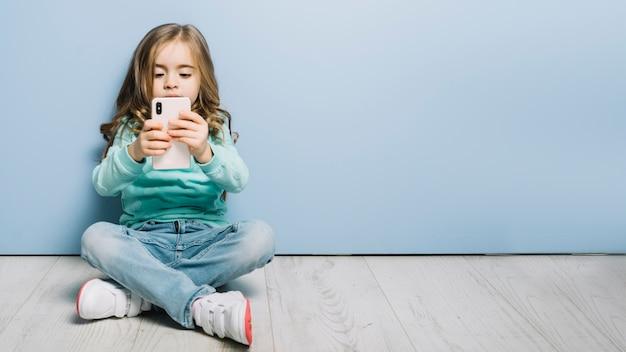 Ritratto di una bambina seduta sul pavimento in legno guardando smartphone Foto Gratuite