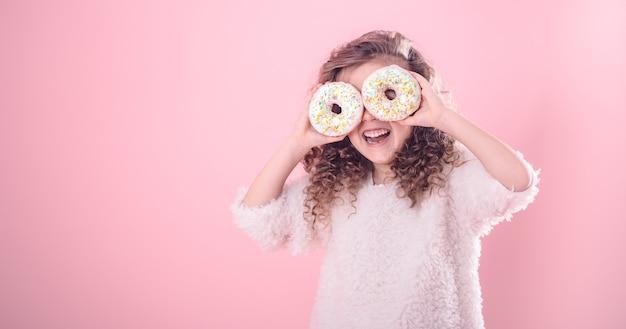 Ritratto di una bambina sorridente con ciambelle Foto Gratuite