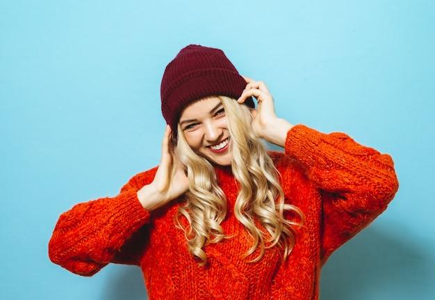 Ritratto di una bella donna bionda che indossa un cappello ed è vestito con un maglione rosso e mostrando la moda si sposta su sfondo blu Foto Premium