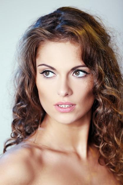 Ritratto di una bella donna bruna con i capelli ricci e le ...