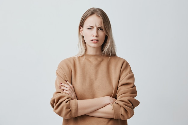 Ritratto di una bella donna con i capelli lisci biondi che aggrotta le sopracciglia con disappunto, indossa un maglione a maniche lunghe sciolto, tenendo le braccia conserte. attraente giovane donna in posizione chiusa. Foto Gratuite