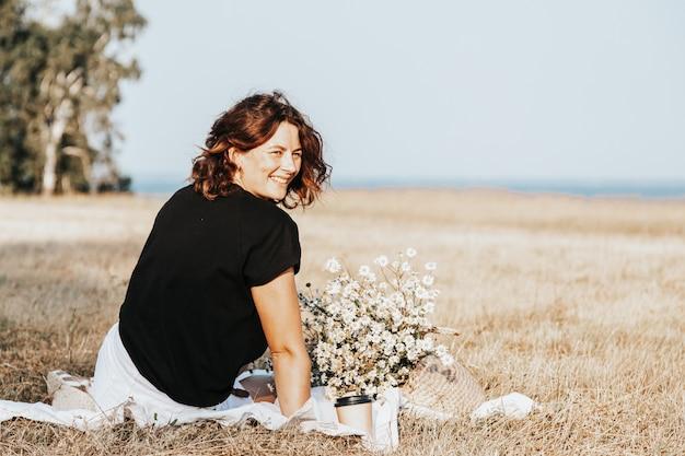 Ritratto di una bella donna con un mazzo di fiori che riposa su un tappeto nei campi Foto Premium