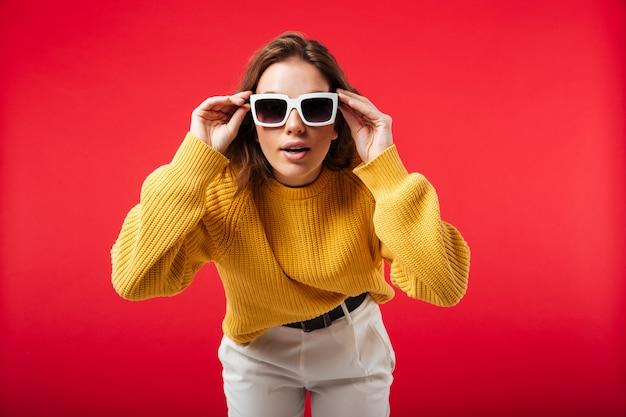 Ritratto di una bella donna in posa con occhiali da sole Foto Gratuite