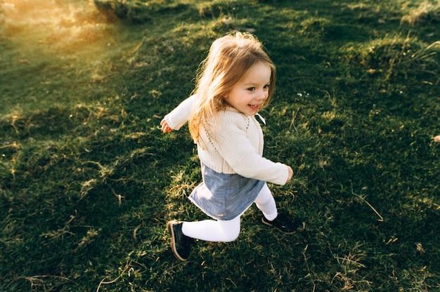 Ritratto di una bella ragazza bella e felice che attraversa il campo soleggiato Foto Premium