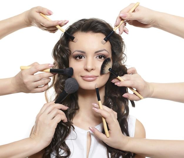 Ritratto di una bella ragazza bruna con i capelli ricci e ondulati lunghi con spazzole per il trucco vicino al viso attraente, molte mani si truccano sul viso di donna isolato su bianco Foto Gratuite