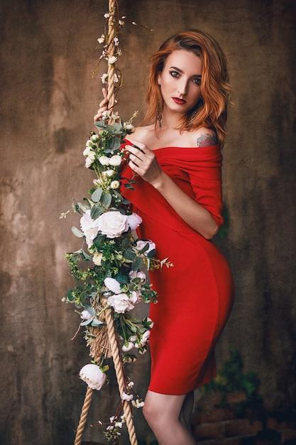 Ritratto di una bella ragazza con i capelli rossi in un abito rosso. Foto Premium