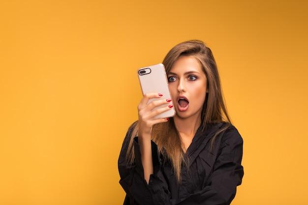 Ritratto di una bella ragazza con un telefono wooku su giallo Foto Premium
