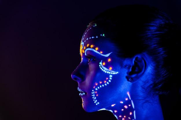 Ritratto di una bella ragazza con vernice ultravioletta sul viso. ragazza con trucco al neon in luce di colore. Foto Premium