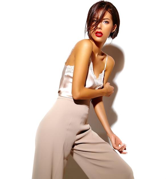 Ritratto di una bella ragazza sensuale donna bruna in eleganti abiti classici bianchi e pantaloni larghi su sfondo bianco Foto Gratuite