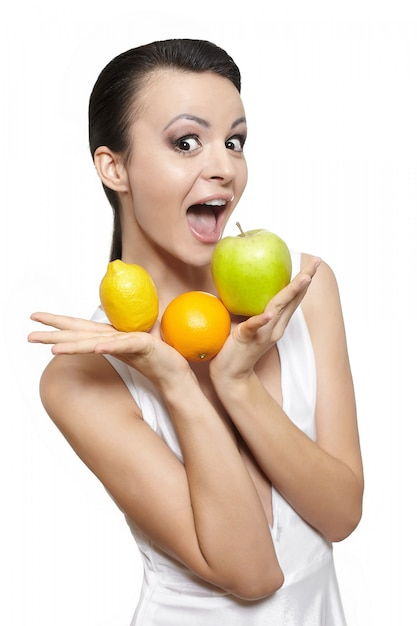 Ritratto di una bella ragazza sorridente felice con frutta limone e mela verde e arancio isolato su bianco Foto Gratuite