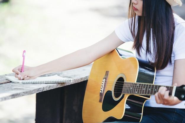 Ritratto di una bella ragazza suonare la chitarra con la scrittura in natura Foto Gratuite