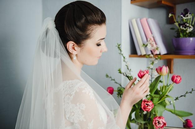 Ritratto di una bella sposa. addebiti al mattino a casa. foto in bianco e nero. matrimonio classico. Foto Premium