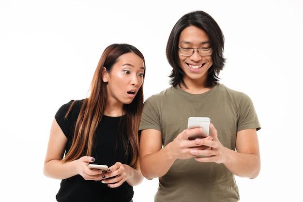 Ritratto di una coppia asiatica abbastanza giovane che per mezzo dei telefoni cellulari Foto Gratuite