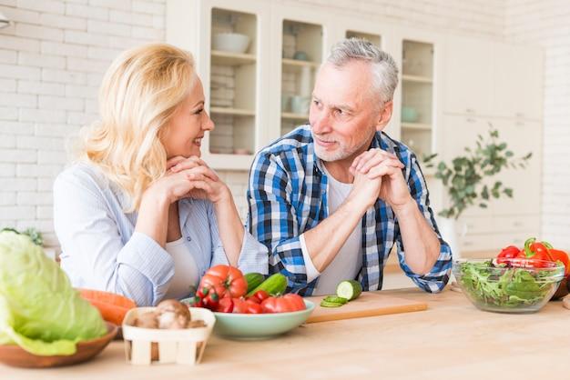 Ritratto di una coppia senior che si appoggia sul tavolo di legno a guardare l'altro in cucina Foto Gratuite