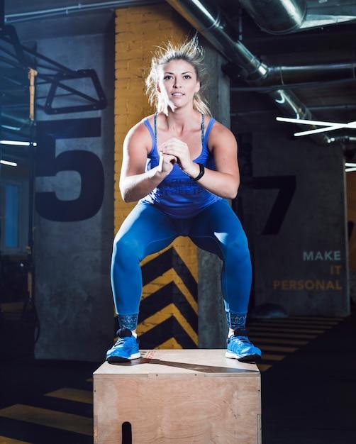 Ritratto di una donna che fa esercizio tozzo sulla scatola di legno nel fitness club Foto Gratuite