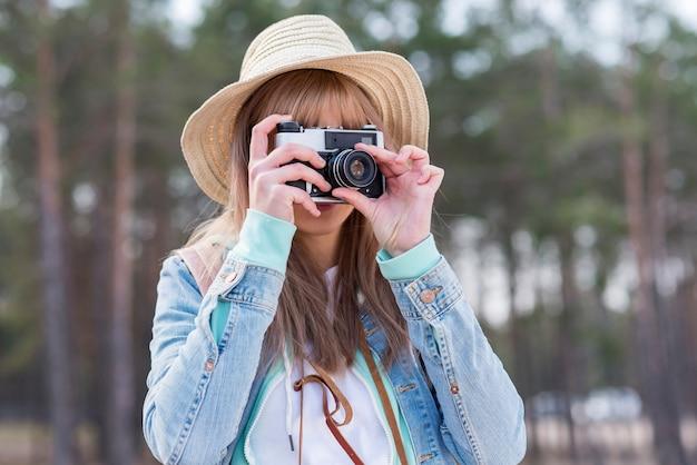Ritratto di una donna che indossa cappello tenendo foto con macchina fotografica d'epoca Foto Gratuite
