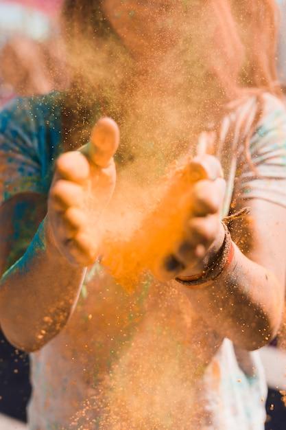 Ritratto di una donna che spolvera la polvere di holi con le mani Foto Gratuite
