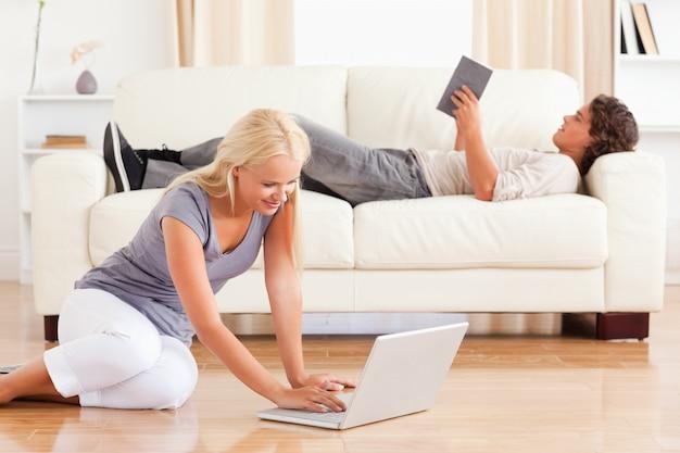 Ritratto di una donna che usa un laptop mentre il suo ragazzo sta leggendo Foto Premium