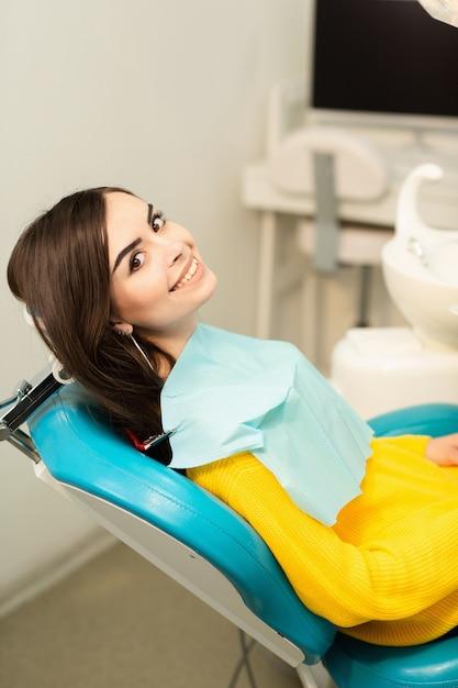 Ritratto di una donna con il sorriso a trentadue denti che si siede alla poltrona del dentista presso lo studio dentistico Foto Premium