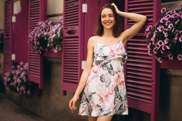 Ritratto di una donna felice al di fuori del caffè decorato con fiori Foto Gratuite