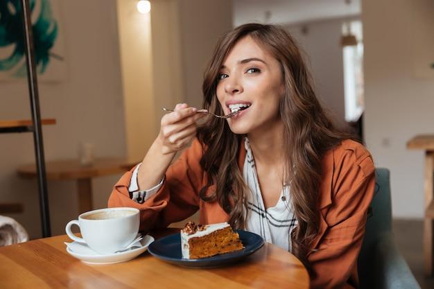 Ritratto di una donna felice che mangia un pezzo di torta Foto Gratuite