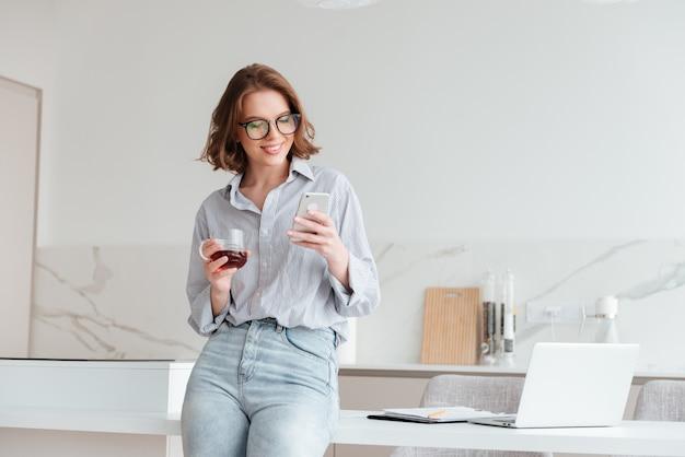Ritratto di una donna felice che per mezzo del telefono cellulare Foto Gratuite