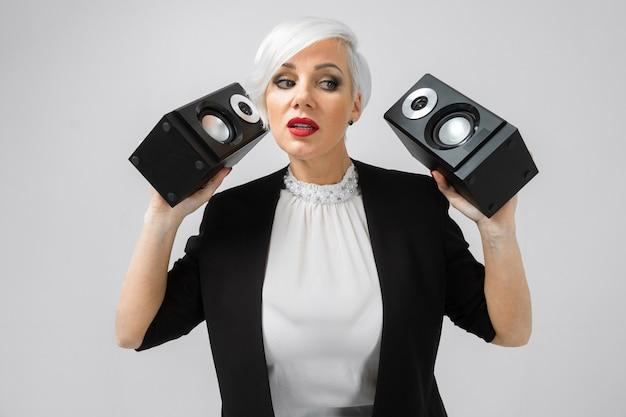 Ritratto di una donna fiduciosa in una tuta con altoparlanti nelle sue mani isolato su uno sfondo chiaro Foto Premium