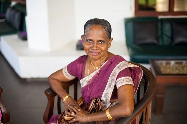 Ritratto di una donna indiana anziana felice in un sari nazionale festivo Foto Premium