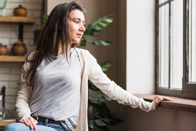 Ritratto di una donna lesbica guardando la finestra Foto Gratuite