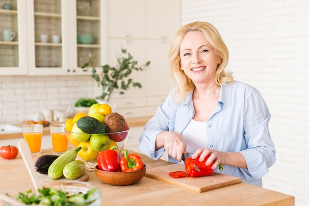 Ritratto di una donna senior che taglia il peperone dolce rosso con il coltello sul tagliere nella cucina Foto Gratuite