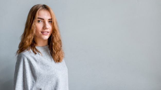 Ritratto di una donna sorridente in piedi contro il muro grigio guardando la fotocamera Foto Gratuite