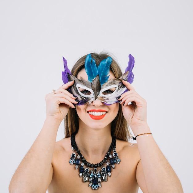 Ritratto di una donna sorridente in topless che indossa la maschera di piume su sfondo bianco Foto Gratuite