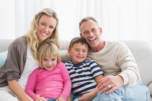 Ritratto di una famiglia allegra sul couche a casa nel soggiorno Foto Premium