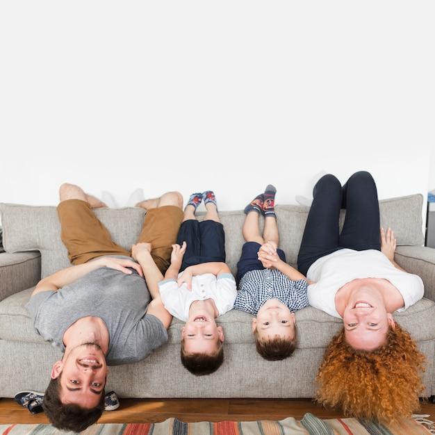 Ritratto di una famiglia felice sdraiato a testa in giù sul divano Foto Gratuite