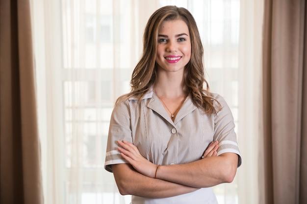 Ritratto di una giovane cameriera sicura sorridente nella camera d'albergo Foto Gratuite