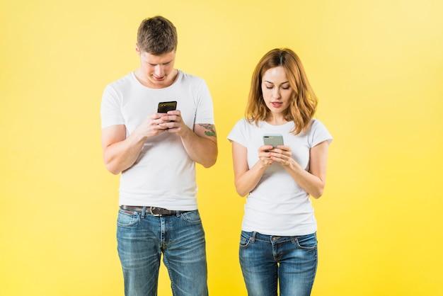 Ritratto di una giovane coppia di sms su smart phone contro sfondo giallo Foto Gratuite