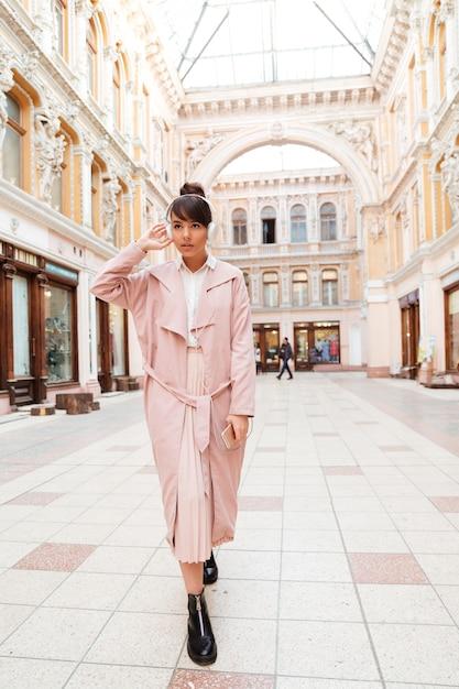 Ritratto di una giovane donna alla moda in cappotto rosa Foto Gratuite