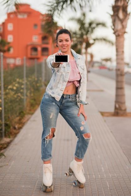 Ritratto di una giovane donna alla moda in piedi sul marciapiede, mostrando il telefono cellulare Foto Gratuite