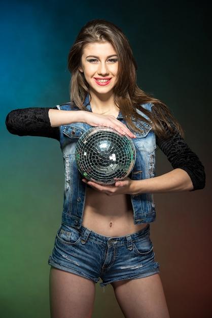 Ritratto di una giovane donna attraente con palla a specchio. Foto Premium